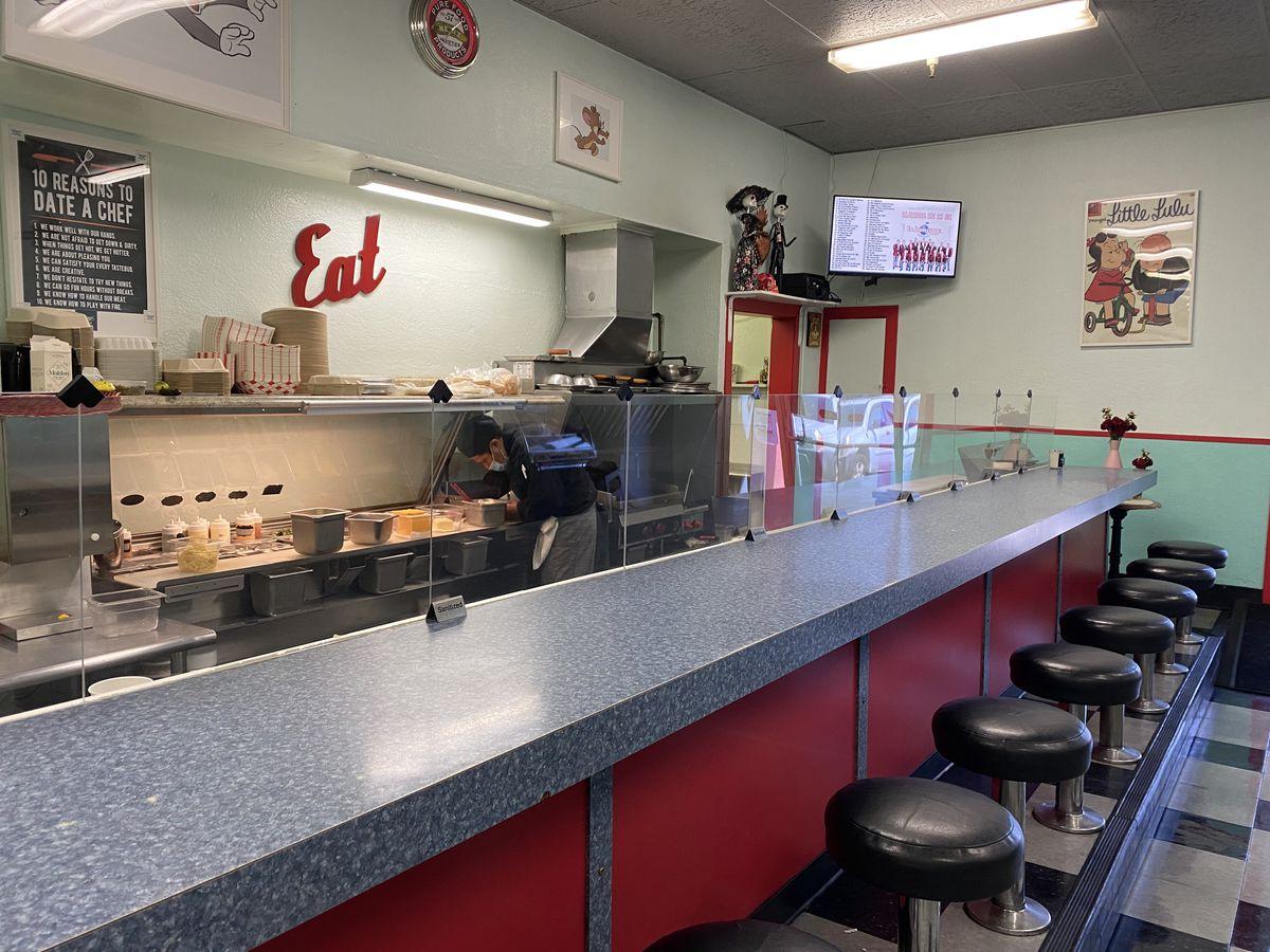 Diseño interior estilo restaurante retro en Lane 33 Café con encimeras de formica gris y taburetes negros.
