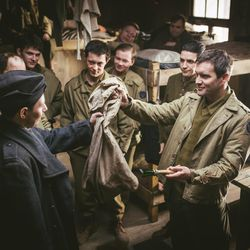 """Jack Ashton, right, acting as Clair Cline, trades for a glass carving tool to make a violin in a prisoner-of-war camp, as seen in """"Instrument of War."""""""