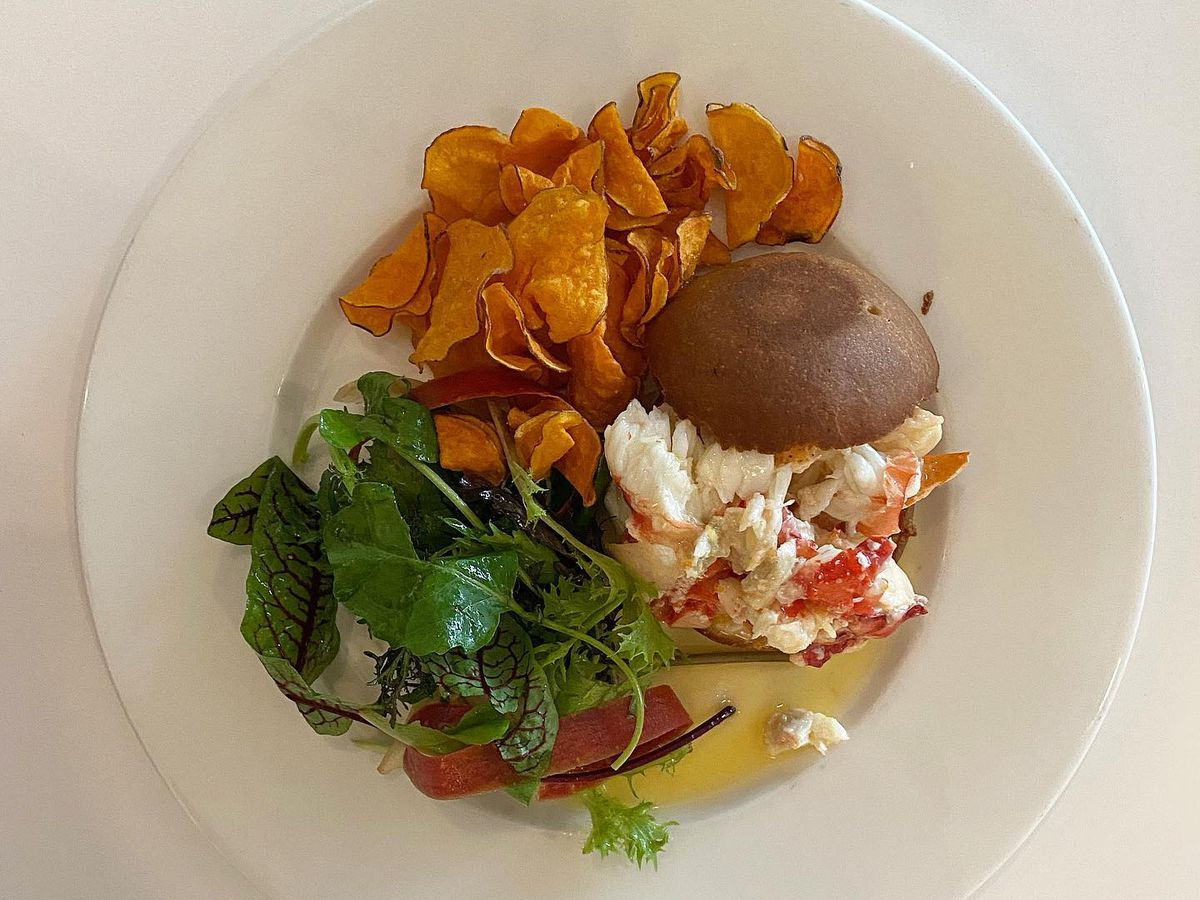 A role with chopped lobster and crab, on a plate with sweet potato chips and greens, on a white tabletop