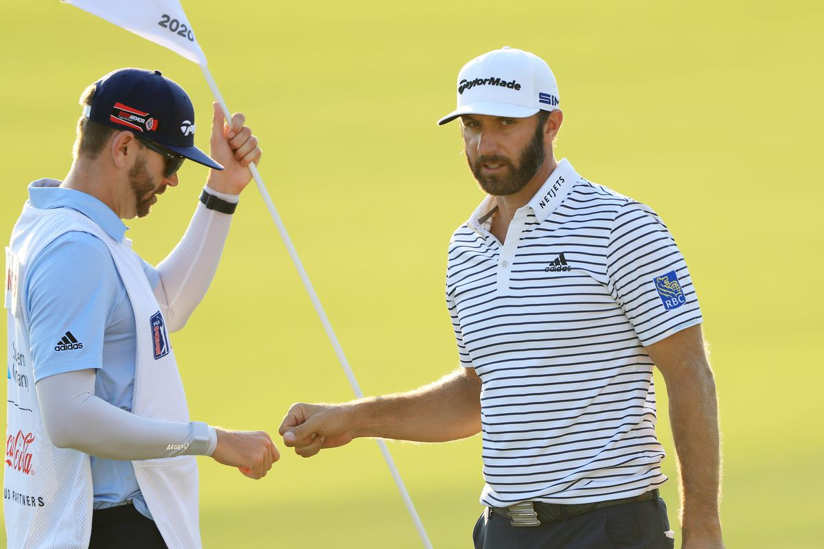 Dustin Johnson of the United States bumps fists with his caddie and brother Austin Johnson on the 18th green during the third round of the TOUR Championship at East Lake Golf Club on September 06, 2020 in Atlanta, Georgia.