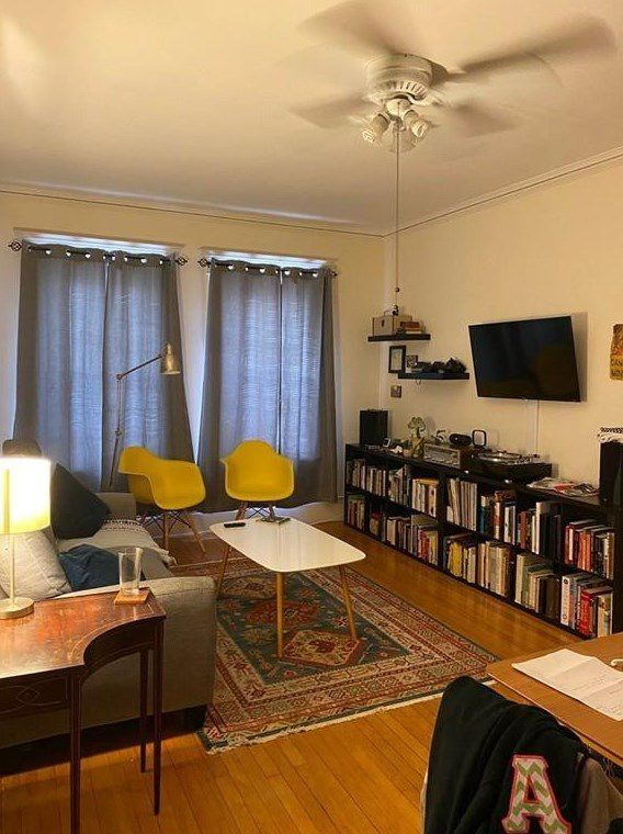 A living room with a couch and two chairs arranged sort of opposite long shelves with a TV mounted above them.