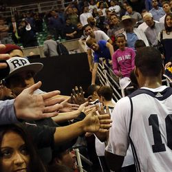 Alec Burks slaps hands with fans as he leaves following the Utah Jazz's scrimmage in Salt Lake City, Saturday, Oct. 5, 2013.