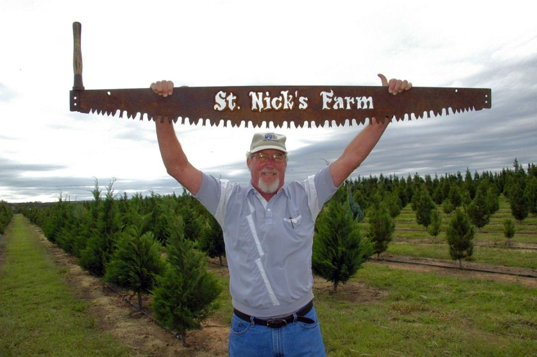 Man holding big saw in front of little trees