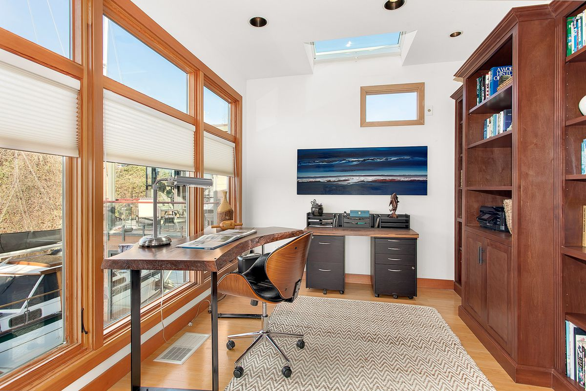 A small office with floor to ceiling windows overlooking a dock