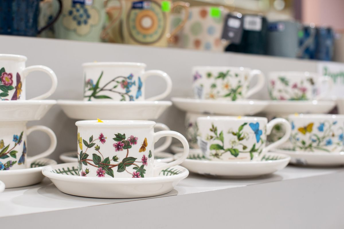 Eight pairs of white saucers and cups with floral decorations on the side.