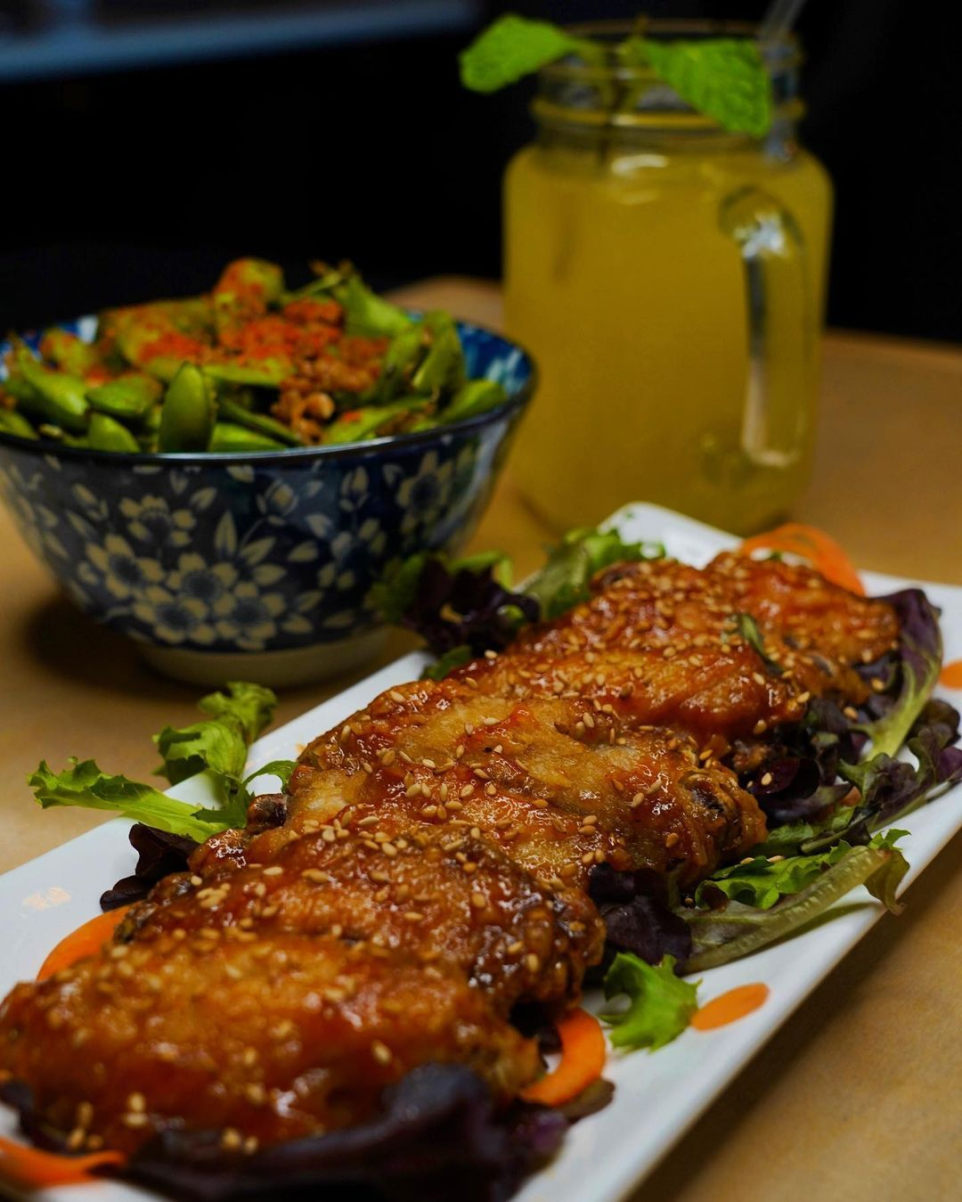 A glazed piece of meat sits atop a small salad of greens. In the background, a bowl of edamame is topped with red seasoning.