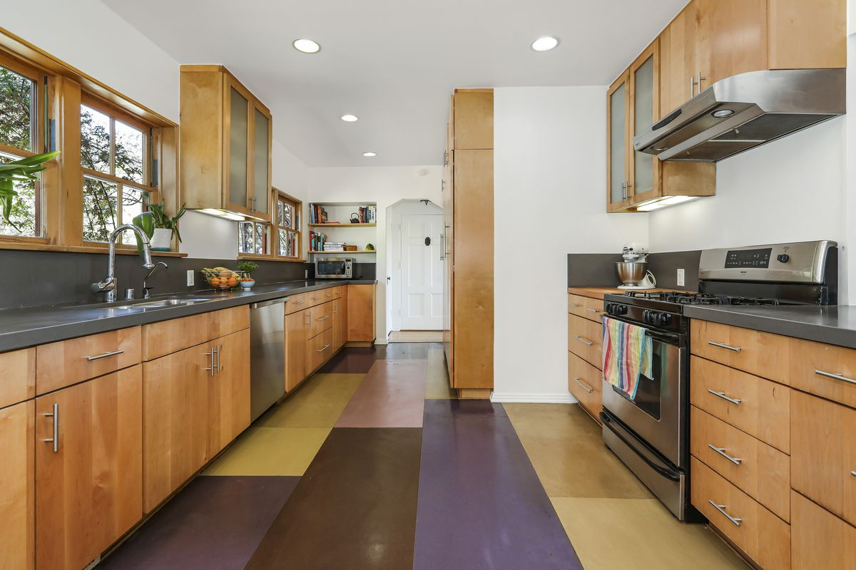 A galley-style kitchen with two long countertops and a sink opposite a stove