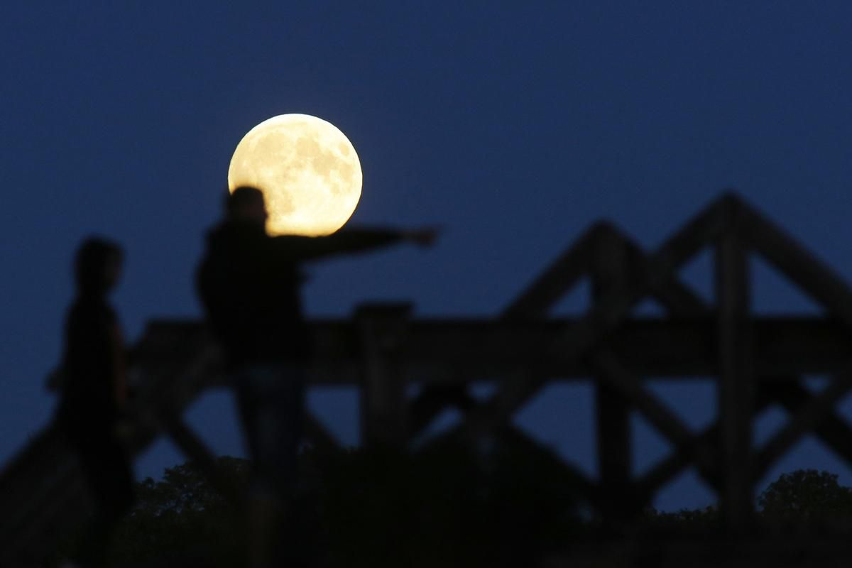 """People watch a perigee moon, also known as a super moon, rises in Mir, Belarus, 95 kilometers (60 miles) west of capital Minsk, Belarus, late Sunday, Sept. 27, 2015. The full moon was seen prior to a phenomenon called a """"Super Moon"""" eclipse that will occu"""