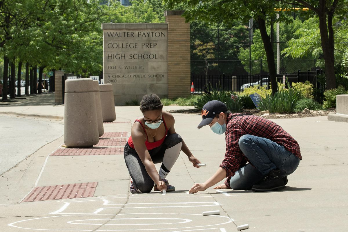 """Benny Chan, a senior at Walter Payton College Preparatory High School, right, writes """"protect our teachers"""" on the sidewalk outside the school in the Near North neighborhood, Thursday morning, May 20, 2021."""