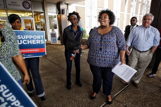 Amber Sherman, center, speaks with a group of school voucher supporters in 2016 after they crashed her press conference in Memphis.