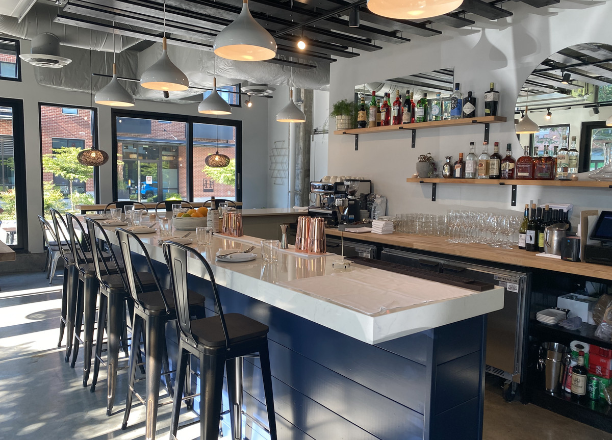 The interior of Autumn restaurant in Phinney Ridge, with a open shelving behind the bar, metal seating, and white and blue accents