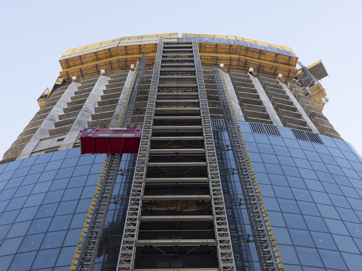 A building under construction with a construction elevator.