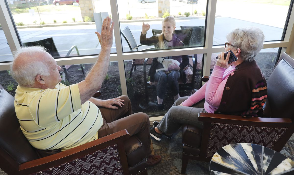 Creekside Assisted Living and Senior Center residents Gordy Call waves to Sally Taylor as her grandmother, Judy Taylor, talks to her by cellphone in Bountiful on Friday, March 27, 2020. Family of residents come to the window to see and talk to them via a cellphone due to Covid-19 restrictions.