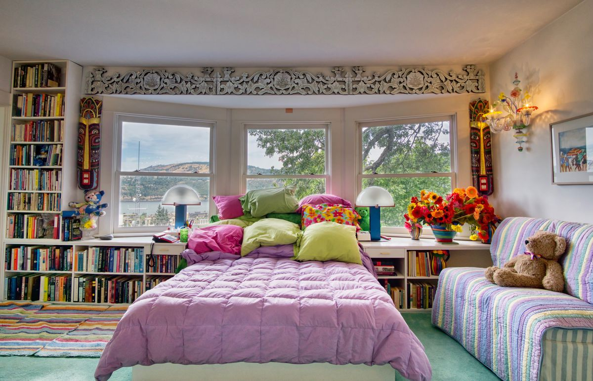 A pink bed sits in front of a bay window with bookshelves and teal floors.