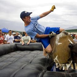 Cameron Lyon of South Jordan rides the mechanical bull while his buddies watch him Wednesday at the Salt Lake County Fair in South Jordan.