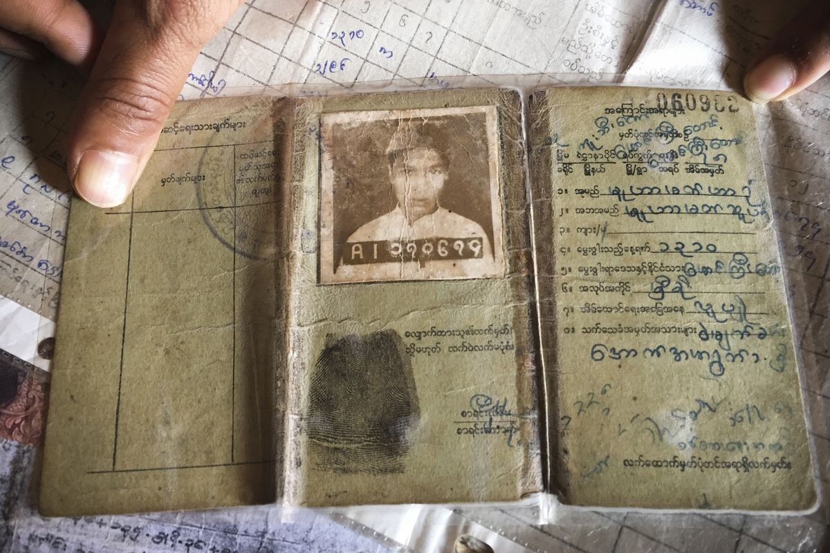 A three-panel Burmese identity document showing a picture, a thumbprint, and a citizenship number.
