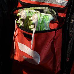 Un par de botines cuelgan del bolso de un repartidor.