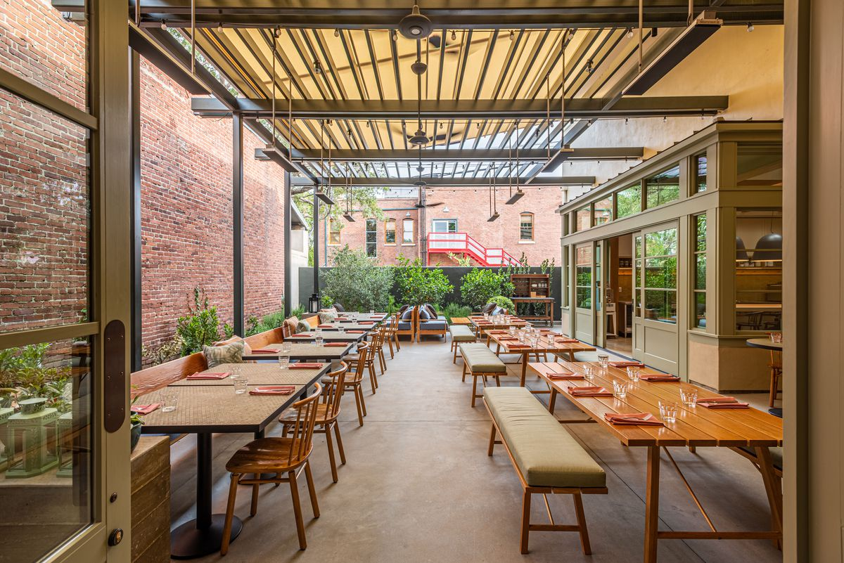 A long back patio with sunlight streaming in, booths to one side, and tables in the middle.