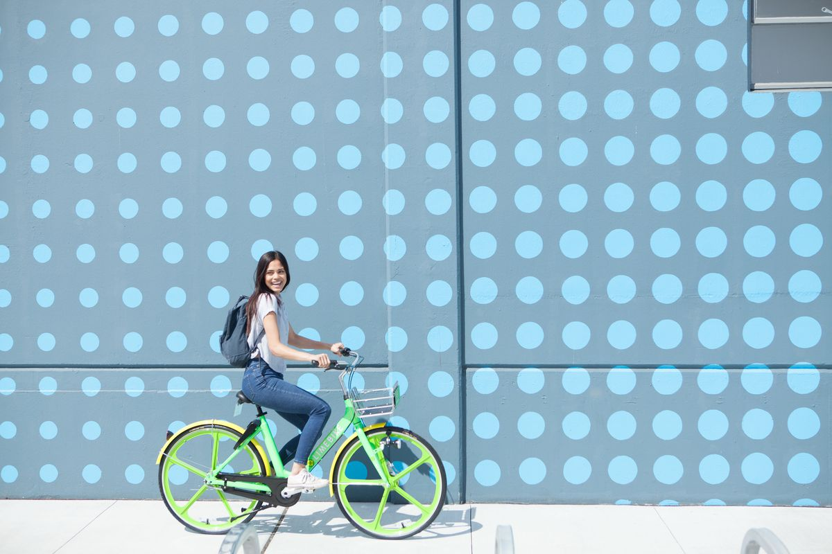 A woman on a green LimeBike bike in front of a blue polkadot wall.
