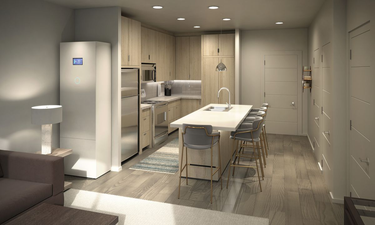 A sleek white and beige kitchen inside a contemporary apartment building; a home battery unit stands near the refrigerator and kitchen island.