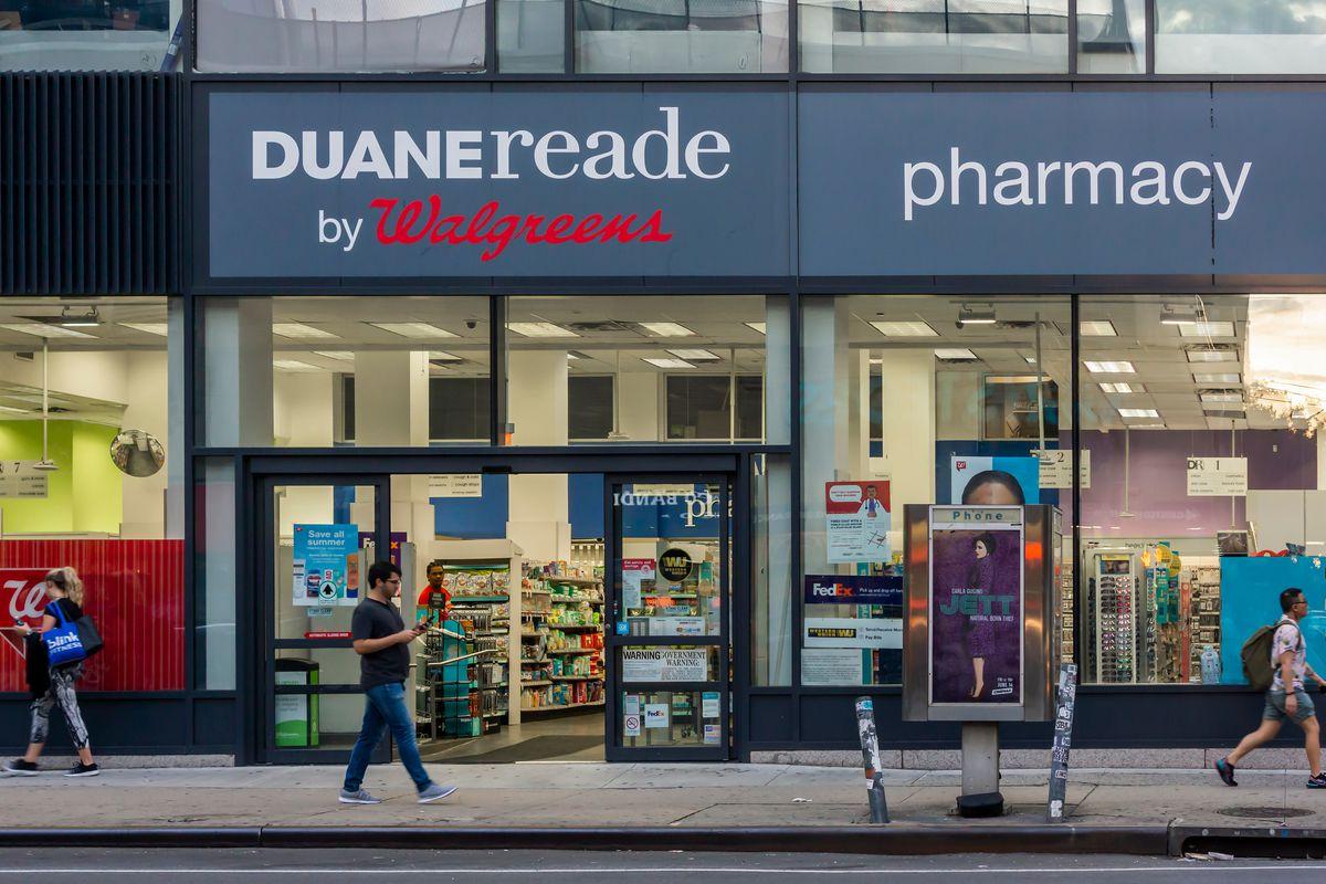 "Pedestrians walk past a store that reads ""Duane Reade."""
