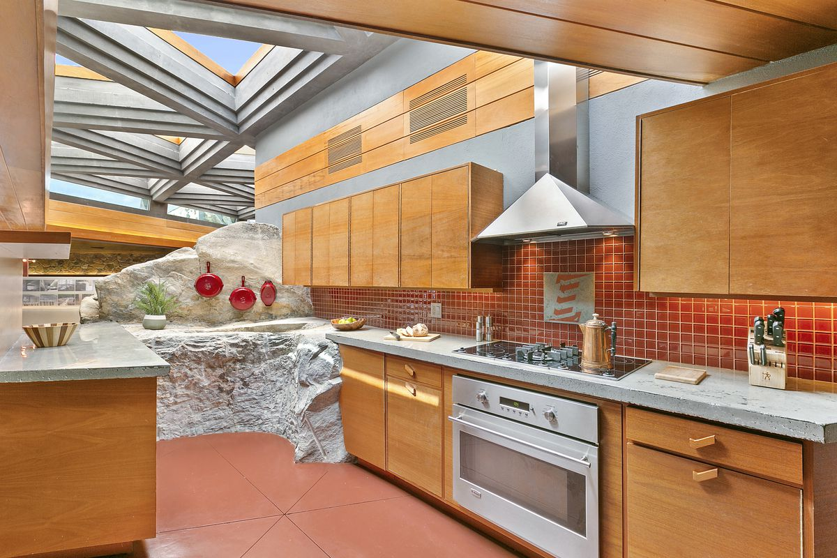 A kitchen with exposed rock ledges, wooden cabinetry, and geometric skylights.
