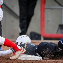 Utah infielder Heather Bowen (37) has the ball before BYU infielder Caitlyn Larsen Alldredge (18) is able to dive safely onto first as the University of Utah hosts Brigham Young University at Duke Stadium in Salt Lake City on Wednesday, April 18, 2018.