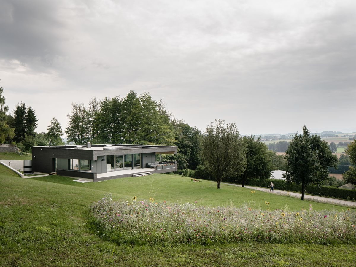 A single-story house sits on a green hill, with mountains in the distance.