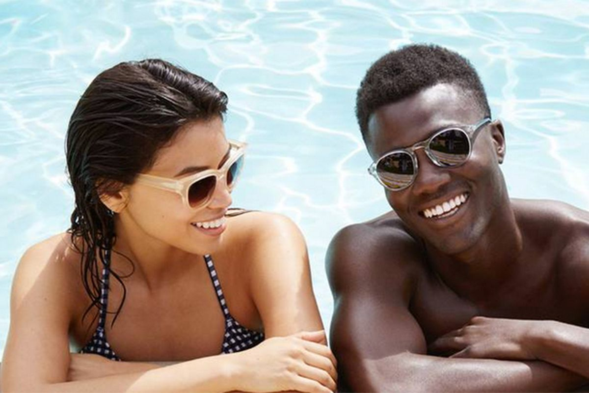 Two people in a pool wearing sunglasses