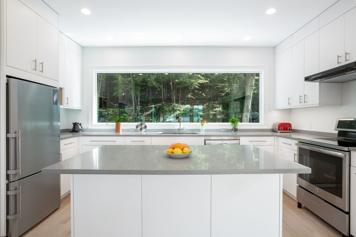 The kitchen features white cabinets, gray counters, stainless steel appliances, and a large window running along the back wall.