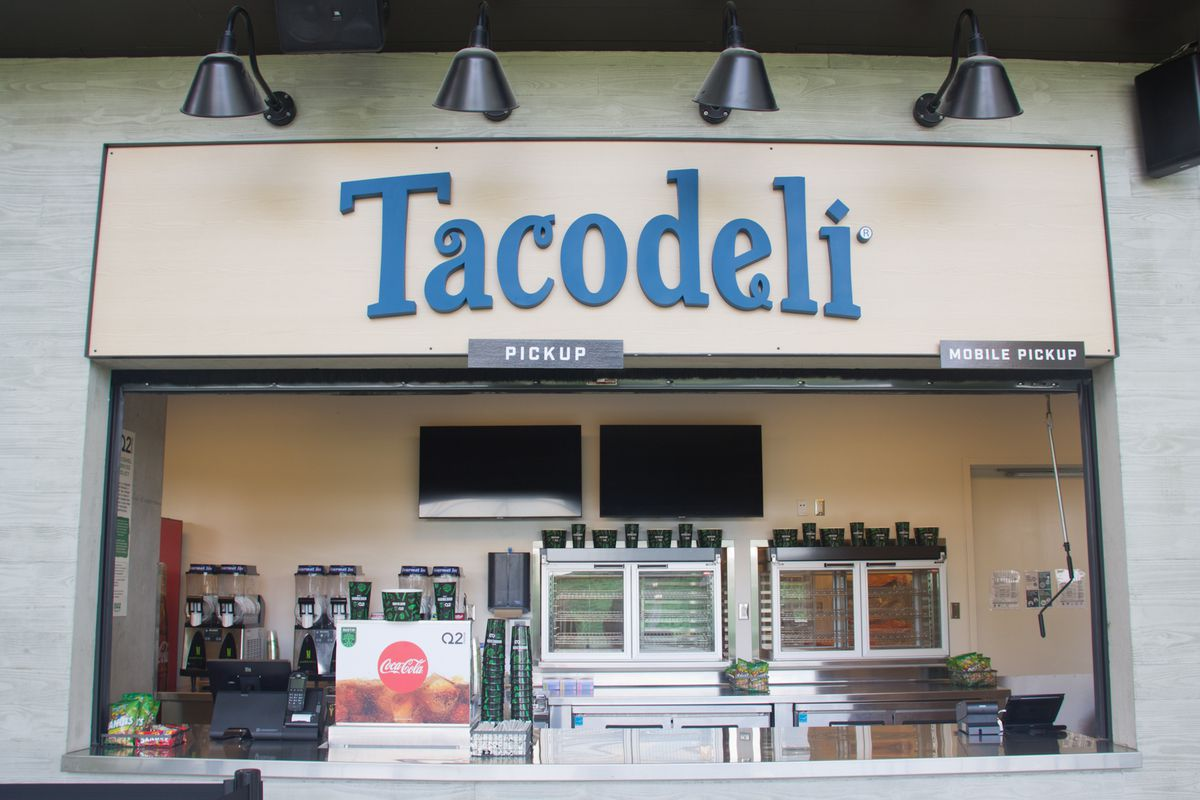 """A stadium concession stand storefront, with a counter, heated containers of food, and a sign that reads """"Tacodeli"""""""