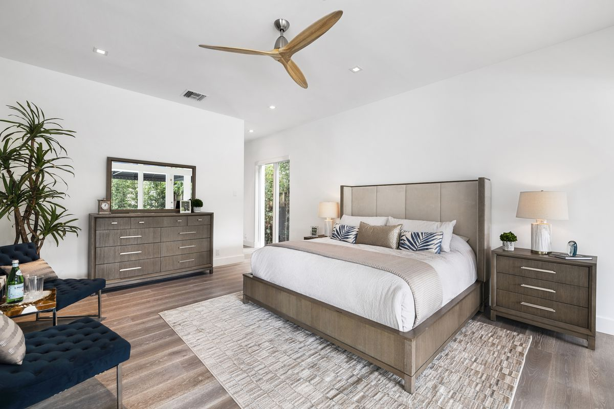 A neutral bedroom with bed, side table, dresser, and small seating area.