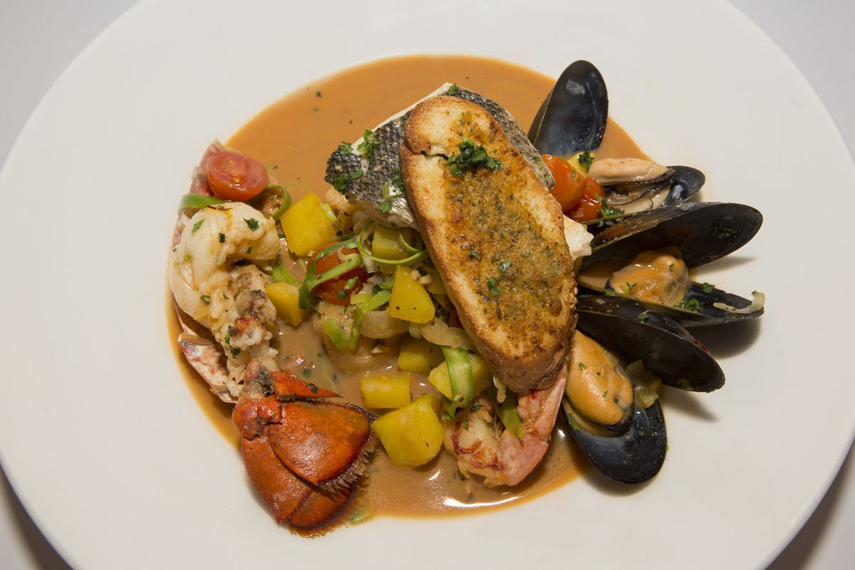 A stew of mussels, multiple types of fish, and vegetables with a slice of toasted bread.