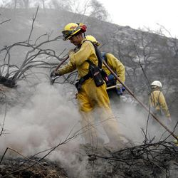 Firefighter James Heaton, front,  hoses down hotspots in the Angeles National Forest Wednesday Sept. 5, 2012 near Los Angeles. Fire crews are getting help from rain in battling a 3,800-acre fire in the San Gabriel Mountains northeast of Los Angeles.
