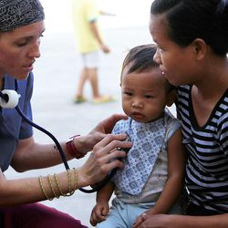 Registered nurse Amber Conlin listens to the heart of Hyrum Wenceslao, Tuesday, Nov. 19, 2013, in Ormoc, Philippines. Hyrum is held by his sister Mary Jane.