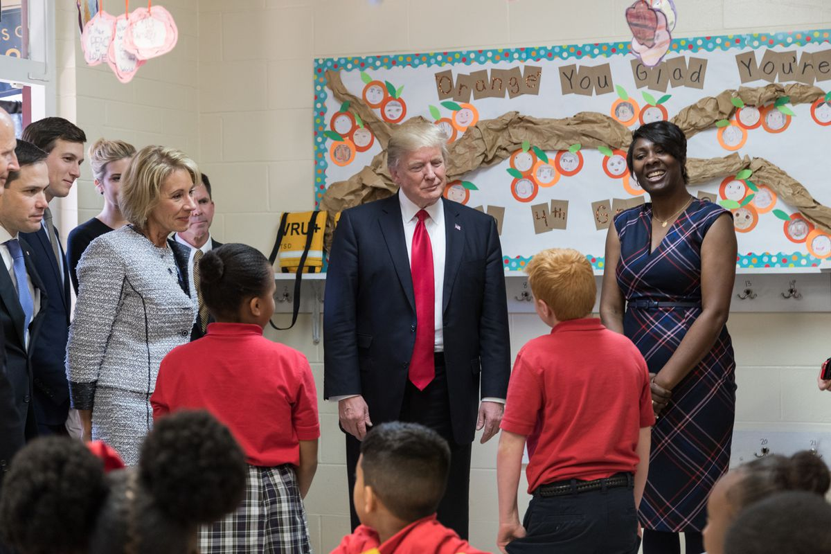 Former President Donald Trump and former U.S. Secretary of Education Betsy DeVos, surrounded by elementary school students and educators, participate in a tour of Saint Andrews Catholic in Orlando, Florida.