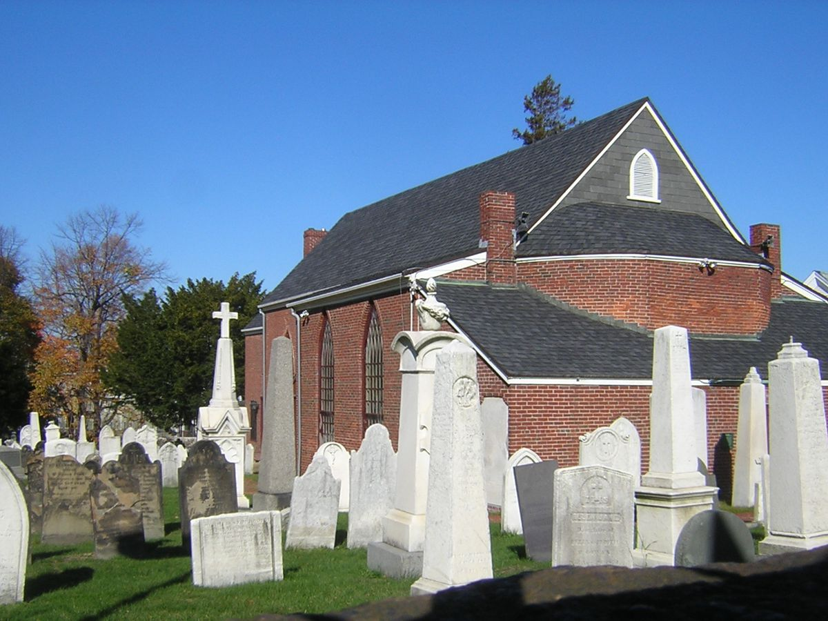 Densely packed headstones and other monuments amid a church with a peaked roof.