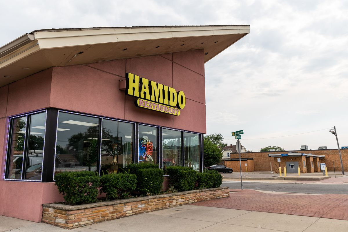 A mid-century building with a pink facade and an A-line, angled roof houses Hamido. The restaurant's sign is yellow.