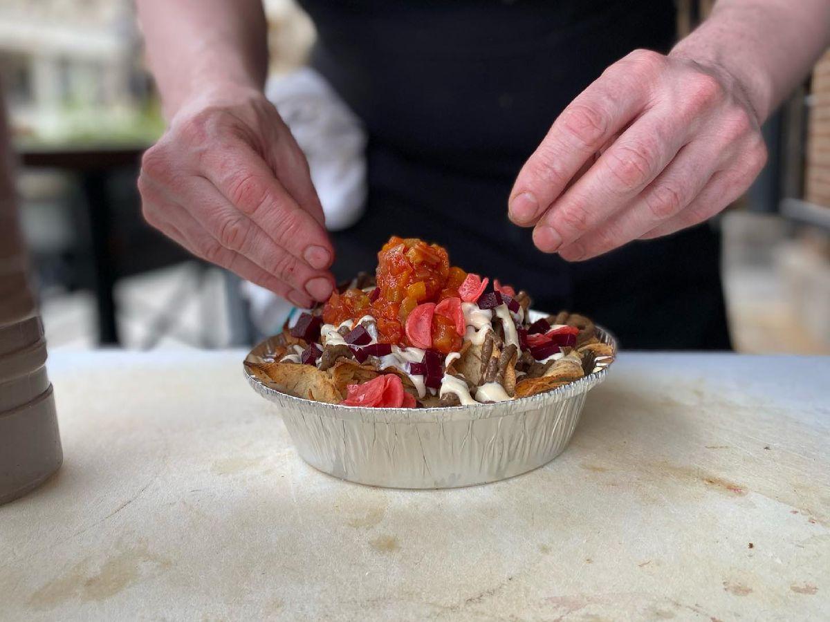 hands preparing food that looks like nachos piled in aluminum dish