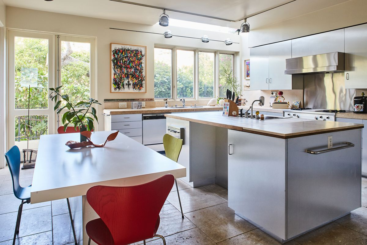 The living room has light colored floors and furniture, allowing the colorful art to pop. The kitchen has a brightly colored painting, and chairs around a breakfast table pick up those hues.