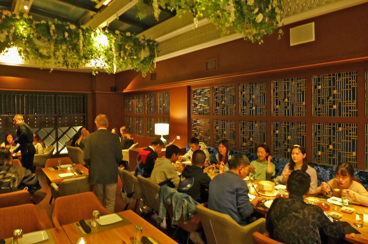 An upstairs dining room with plants hanging from the ceiling, and a giant long table of diners on the right side...