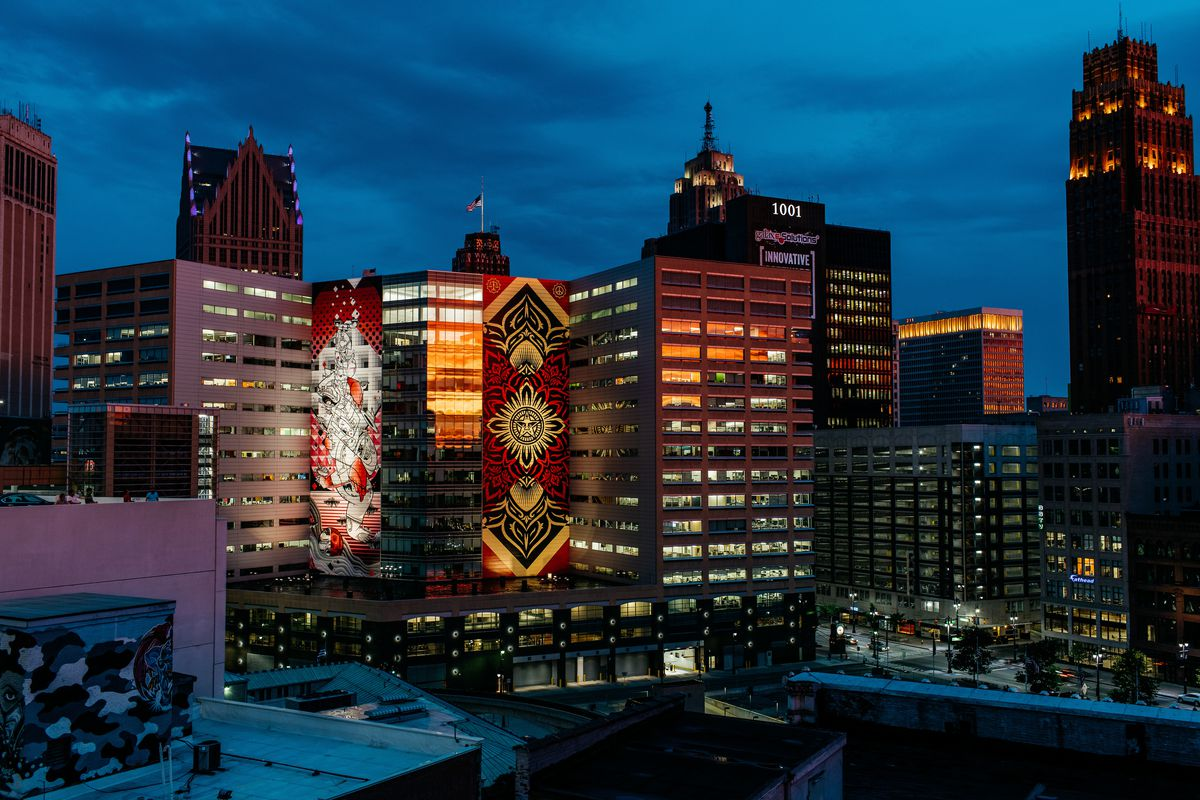 A view of the downtown Detroit skyline at night includes a Shepard Fairey mural.