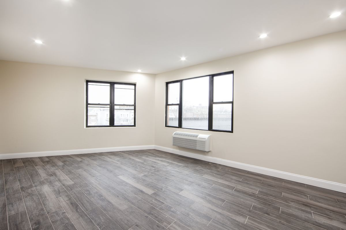 A living area with hardwood floors, two sets of windows, and beige walls.