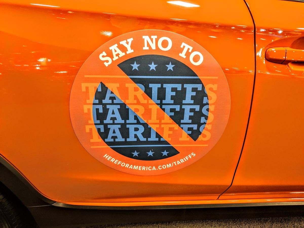 "A ""Say no to tariffs"" sticker is shown on the Washington Auto Show"