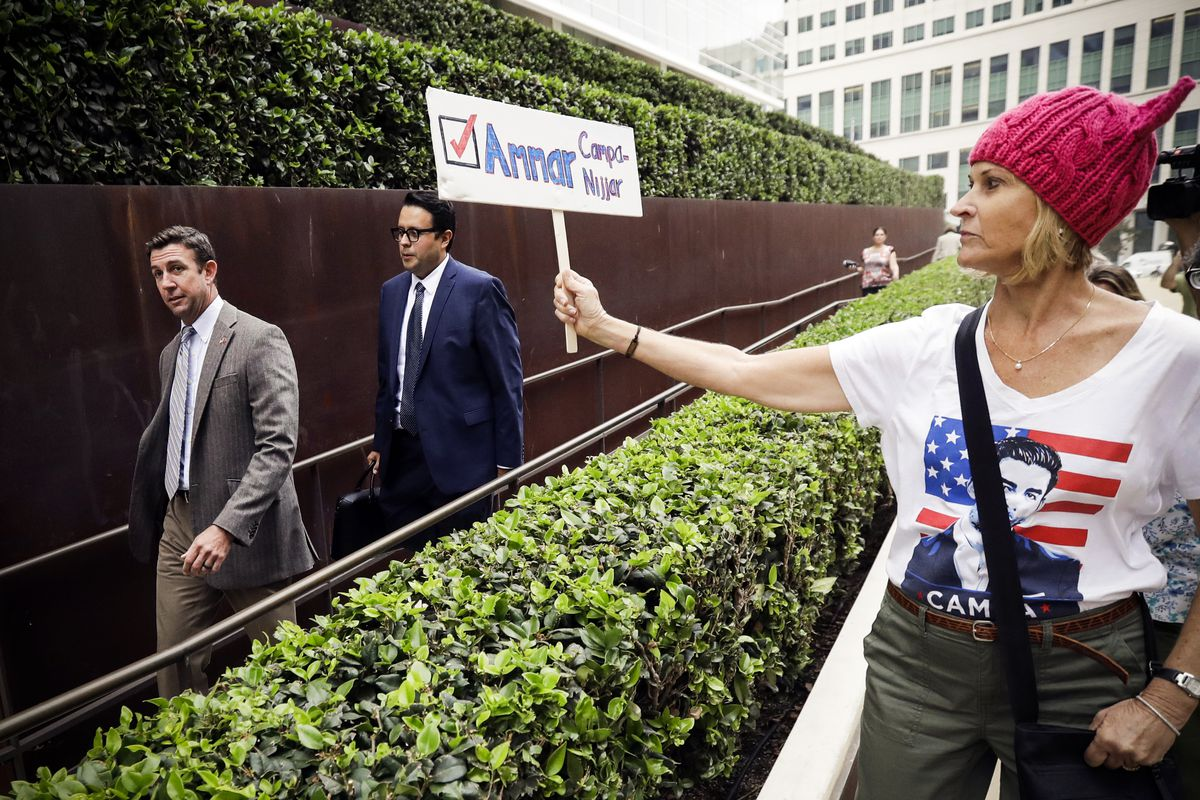 Rep. Duncan Hunter (left) leaves court as a woman holds a sign for Ammar Campa-Najjar in the race for California's 50th district, on Sept. 24, 2018.