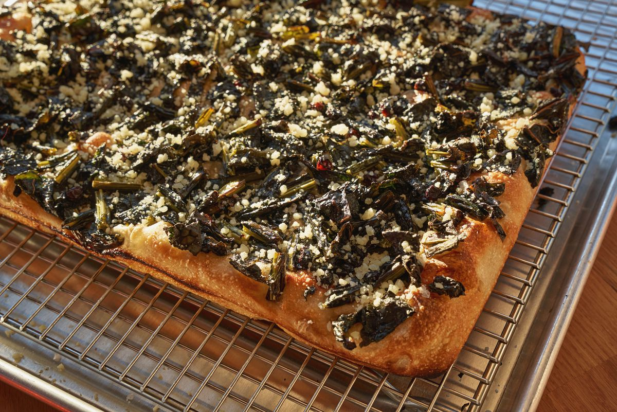 A rectangular slab of focaccia bread topped with green leaves, dots of red currant, and shavings of yellow-white cheese