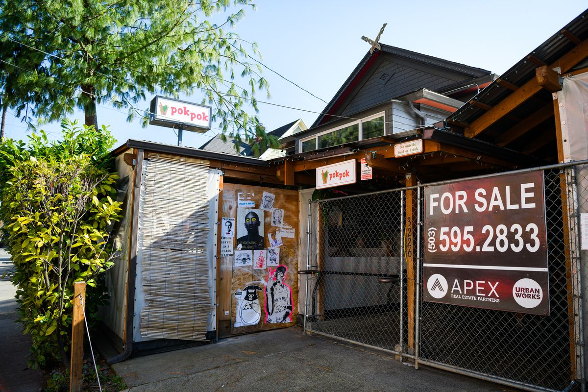 """The entrance to Pok Pok now has a massive """"For Sale"""" sign on a gate blocking its entrance. Plywood blocking another entrance is now covered in posters."""