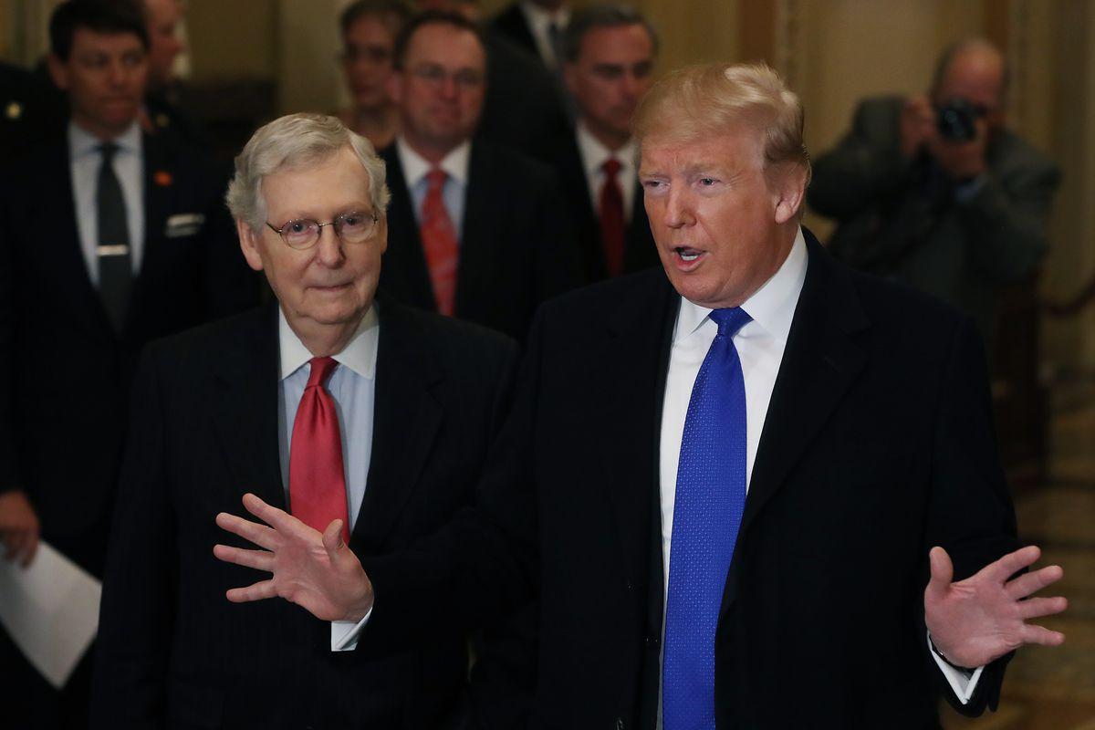 Senate Majority Leader Mitch McConnell standing beside President Donald Trump.