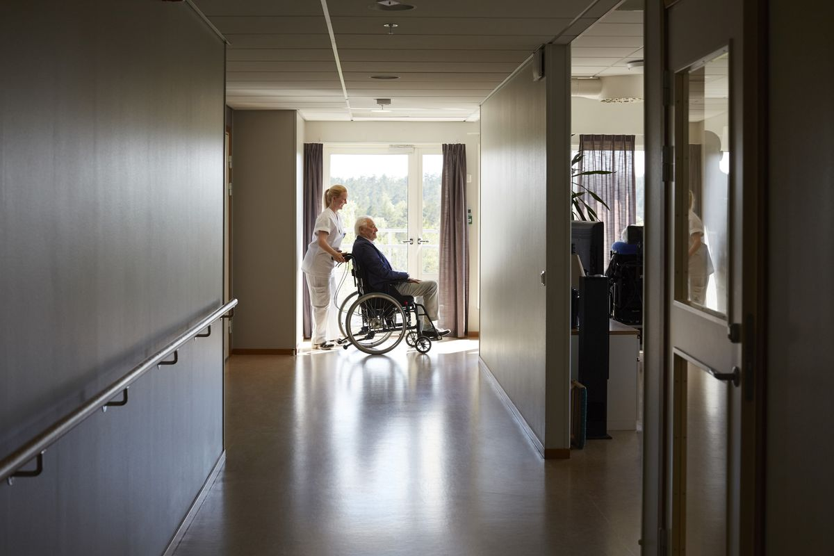 A nurse pushing a patient in a chair at the end of a nursing home hallway.