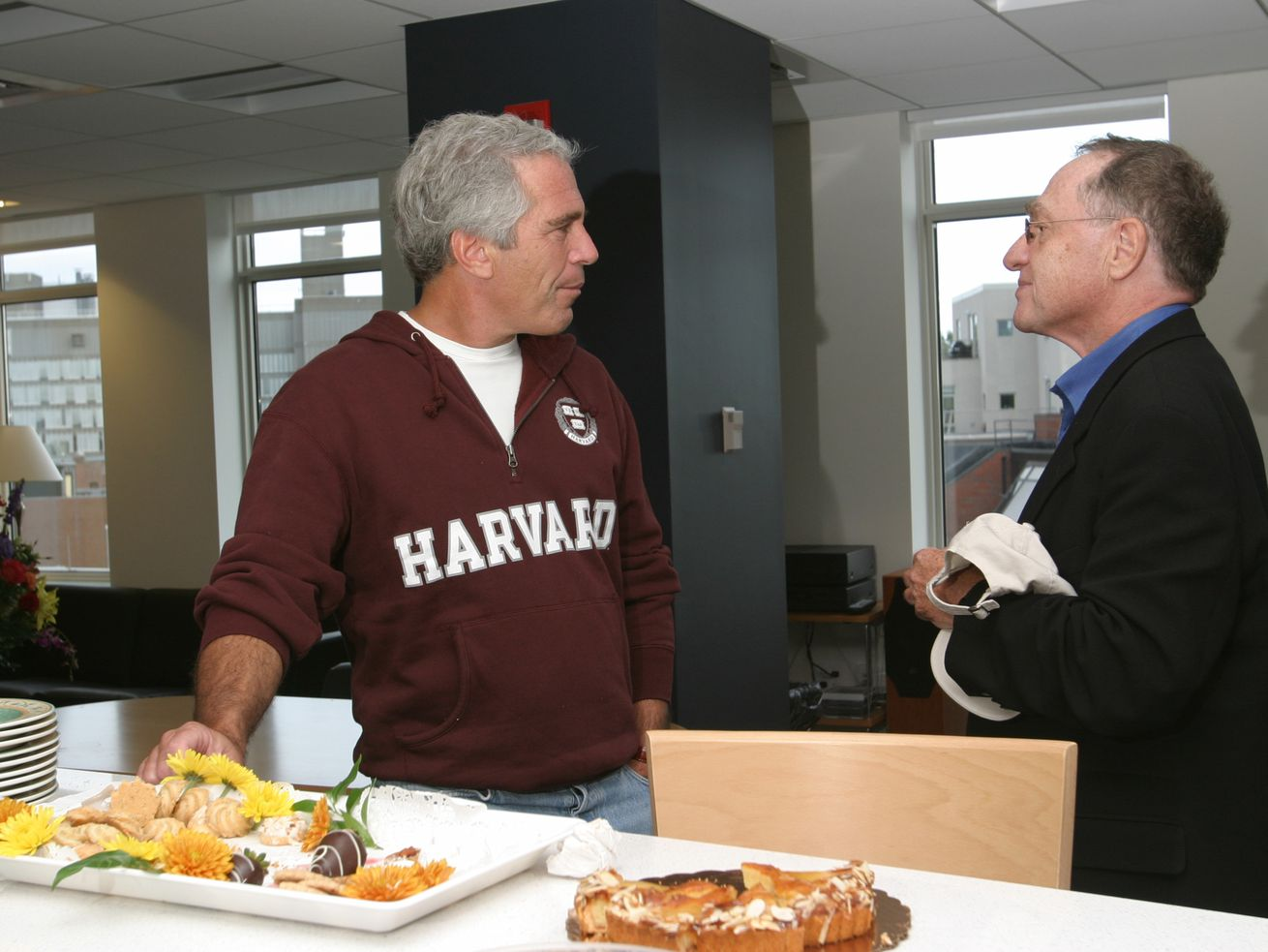 In this photograph from 2004, convicted sex offender Jeffrey Epstein speaks with then-Harvard professor Alan Dershowitz, who would later serve on Epstein's defense team.